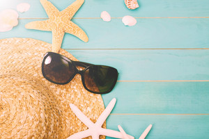 Sunglasses with sea shells and straw hat on light blue wooden background