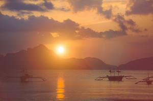 Sunset at El Nido. Banca boat anchored in a bay. Palawan island, Philippines