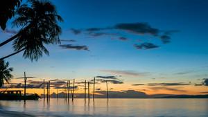 Sunset on Kri Island. Boats under Palmtrees. Raja Ampat, Indonesia, West Papua