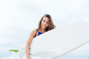 Surfer young girl with sexy fit body in swimsuit holding surfboard