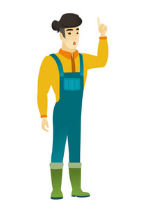 Surprised asian farmer in coveralls with open mouth pointing finger up. Full length of young farmer with open mouth came up with an idea. Vector flat design illustration isolated on white background.