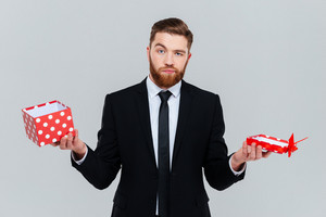 Surprised bearded business man in suit holding empty open gift in hands. Isolated gray background