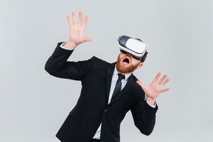 Surprised bearded business man in suit using virtual reality device. Isolated gray background