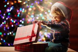 Surprised boy looking at xmas present in red giftbox