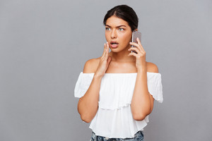 Surprised brunette woman talking on the phone isolated on a gray background