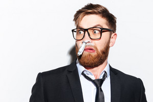 Surprised Business man in glasses and suit sniffing cocaine. Stoned Man with bank note in nose looking aside. Isolated gray background