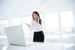 Surprised Business woman standing near the table, looking at laptop and talking at phone in office