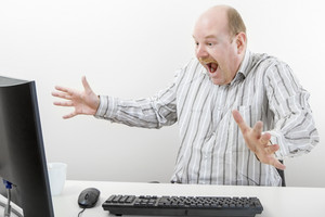 Surprised Businessman Gesturing While Looking At Computer