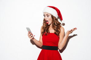 Surprised charming young woman in santa costume with hat looking at smartphone over white background