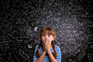 Surprised girl  in blue striped t-shirt covering her mouth with both hands against big blackboard with mathematical symbols and formulas