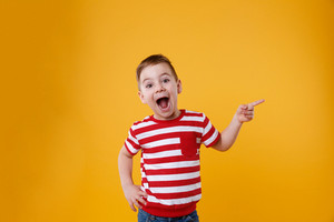 Surprised happy boy pointing fingers up at copyspace isolated over orange background
