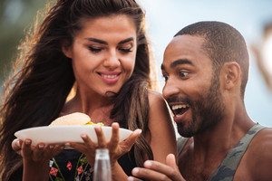 Surprised hungry young couple with fresh hamburger outdoors