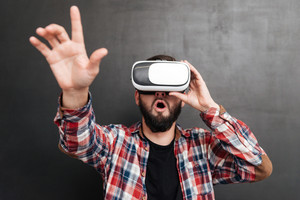 Surprised man dressed in shirt in a cage and wearing virtual reality device standing over chalkboard