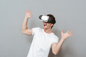 Surprised man wearing virtual reality device in studio and showing surprised gesture of his hands. Isolated gray background