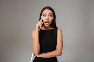 Surprised pretty woman in black dress talking on the mobile phone over gray background
