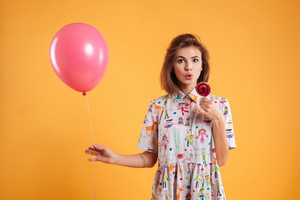 Surprised pretty young woman holding pink balloon and eating lollipop over yellow background