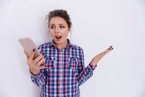 Surprised Woman in checkered shirt holding phone with open mouth. Isolated gray background