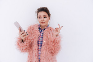Surprised Woman in fur coat holding phone and looking at him. Isolated gray background