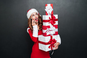 Surprised woman with gifts talking on phone and looking away over black background