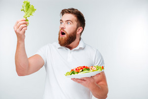 Surprised young bearded man holding plate with fresh salad isolated on white background