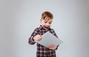 Surprised Young boy in shirt using tablet computer with open mouth. Isolated gray background