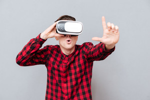 Surprised young man in virtual reality device showing photo sign. Isolated gray background
