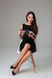 Surprised young woman in black dresss reading news in magazine over gray background