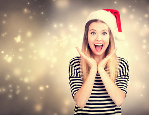 Surprised young woman with Santa hat posing in shiny blue night background