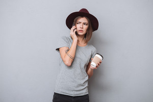 Suspicious young girl holding cup of coffee and talking on mobile phone isolated on a gray background
