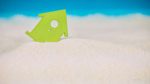 Symbol House Built on Sand, Small Green Symbol of an House Sinking into the Sand