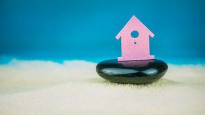 Symbol of little lilac house secured builed on black stone on blue background