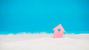 Symbol of little red house on the sand with bright blue background