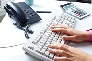 Table with a telephone, calculator, computer keyboard and female hands typing on it