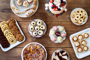 Table with cake, pie, cupcakes, cookies, tarts and cakepops. Studio shot on brown wooden background. Flat lay.