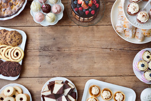 Table with cake, pie, cupcakes, tarts and cakepops. Frame composition. Studio shot on brown wooden background. Copy space. Flat lay.