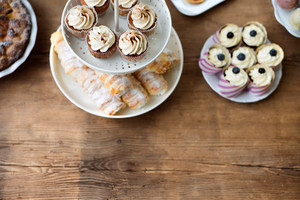 Table with cupcakes, horn pastries, pie and other treats. Studio shot on brown wooden background. Copy space. Flat lay.