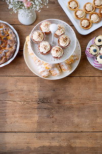 Table with cupcakes, tarts, pie and horn pastries. Studio shot on brown wooden background. Copy space. Flat lay.