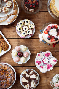 Table with loads of cakes, cupcakes, cookies, pie and cakepops. Studio shot on brown wooden background. Flat lay.