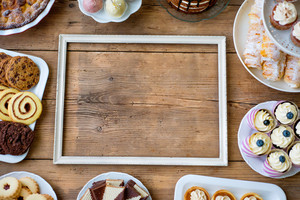 Table with picture frame, cake, cupcakes, cookies, pie, tarts and cakepops. Studio shot on brown wooden background. Copy space. Flat lay.
