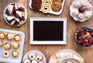 Table with picture frame, cake, cupcakes, tarts, cookies and cakepops. Studio shot on brown wooden background. Copy space. Flat lay.