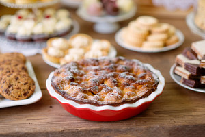 Table with sweet pie, tarts, wafers and chocolate chip cookies. Close up. Studio shot on brown wooden background. Flat lay.