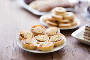 Table with tarts with jam and cream and sandwich jelly cookies among other treats. Close up. Studio shot on brown wooden background.