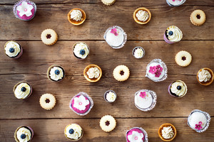 Table with various cupcakes, tarts and cookies. Studio shot on brown wooden background. Flat lay.