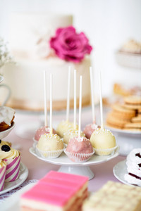 Table with white and pink cake pops on cakestand and various cakes. Candy bar.