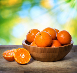 Tangerines in wooden bowl over shiny leaves background