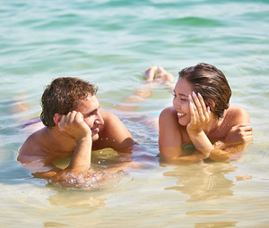 Tanned guy and girl flirting enjoying their resort romance