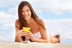 Tanning girl drinking fresh orange juice lying on the beach