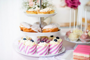 Tarts with meringues, glazed cream puffs or profiterole and cupcakes on cakestand. Cake pops on plate.