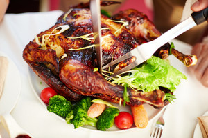 Tasty roasted turkey with vegetables being cut by a human