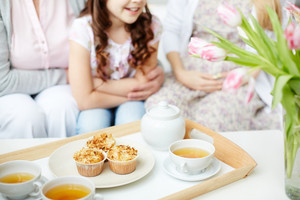 Teacups and cupcakes on tray with little girl, her mother and grandmother on background